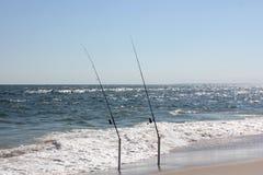 Zwei Angelruten auf dem Strand Stockbild