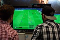 Zwei angemessene Besucher spielen das Spiel Pro Evolution Soccer lizenzfreie stockbilder
