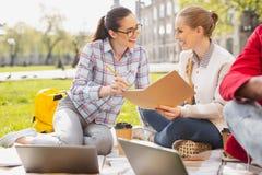 Zwei angenehme Studenten, die draußen zusammen studieren Stockfotografie