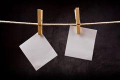 Zwei Anmerkungen des leeren Papiers, die am Seil mit Kleidungsstiften hängen Lizenzfreie Stockbilder