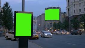 Zwei Anschlagtafeln mit einem grünen Schirm Am Abend auf einer verkehrsreichen Straße stock video footage