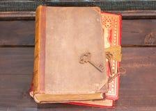 Zwei antike Bücher auf einem hölzernen Regal mit einigen alten Hauptschlüsseln Stockfoto