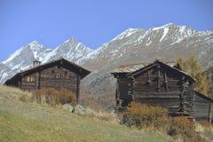 Zwei antike Holzhäuser vom alten Dorf von Zermatt mit Matterhorn ragen in Hintergrund empor Stockbilder