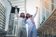 Zwei arabische Geschäftsmänner, die beide Hände oben in der Stadt anhebend bereitstehen, Lizenzfreies Stockfoto