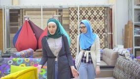 Zwei arabische junge Frauen im hijab wählen Möbel stock footage