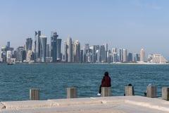 Zwei arabische mittlere Ostern-Frauen, die auf Corniche Broadway sitzen und auf der Doha-Skyline-Ansicht schauen Katar, Mittlere  Stockbilder