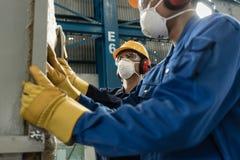 Zwei Arbeiter, die Schutzausrüstung tragen Stockbild