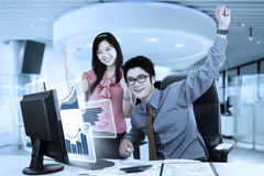 Zwei Arbeitskräfte angehobene Hände im Büro Stockbilder