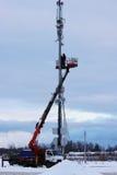 Zwei Arbeitskräfte bauen Ausrüstung für Telekommunikation auf dem Turm mithilfe des Aufzugs im Winter zusammen Stockfotografie