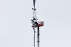 Zwei Arbeitskräfte bauen Ausrüstung für Telekommunikation auf dem Turm mithilfe des Aufzugs im Winter zusammen Lizenzfreies Stockbild