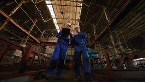 Zwei Arbeitskräfte besprechen ein Bauvorhaben stock footage