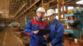 Zwei Arbeitskräfte besprechen ein Bauvorhaben stock video