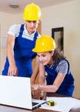 Zwei Arbeitskräfte in den Sturzhelmen mit Laptop Lizenzfreie Stockbilder