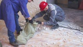 Zwei Arbeitskräfte in der Uniform trägt Taschen des Baurückstands vom Gebäude stock footage