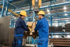 Zwei Arbeitskräfte, die das schwere Laden angehoben durch Kran behandeln stockfoto