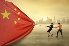 Zwei Arbeitskräfte, die eine chinesische Flagge ziehen Lizenzfreie Stockbilder