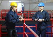 Zwei Arbeitskräfte, die in einer Fabrik sprechen Lizenzfreie Stockfotos