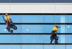 Zwei Arbeitskräfte, die Fenster des modernen Gebäudes waschen Stockfotografie