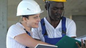 Zwei Arbeitskräfte, die Gespräch haben und Tablet-Computer verwenden lizenzfreie stockfotos