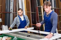 Zwei Arbeitskräfte, die PVC-Fensterprofil wählen Stockfotografie