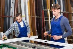 Zwei Arbeitskräfte, die PVC-Fensterprofil wählen Stockfoto