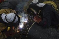 Zwei Arbeitskräfte, die zusammen großes Rohr für Stadtheizung schweißen Lizenzfreies Stockfoto