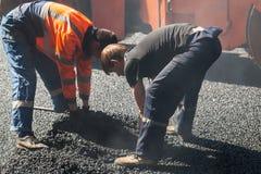 Zwei Arbeitskräfte installieren Abwasserkanaleinsteigeloch Lizenzfreie Stockfotografie