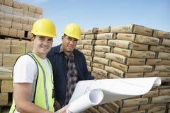 Zwei Arbeitskräfte mit Plan am Standort Stockfoto