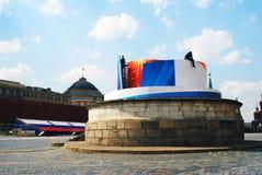 Zwei Arbeitskräfte reparieren eine Feiertagsfahne auf dem Roten Platz in Moskau. Stockbild