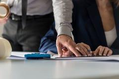 Zwei Architekten bei der Arbeit in ihrem Büro mit dem Mann, der eine Querstation zeigt Lizenzfreies Stockfoto