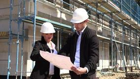 Zwei Architekten in den weißen Sturzhelmen besprechen einen Plan an einer Baustelle stock video