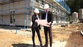 Zwei Architekten in den wei?en Sturzhelmen besprechen einen Plan an einer Baustelle stock video