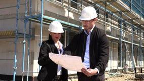 Zwei Architekten in den wei?en Sturzhelmen besprechen einen Plan an einer Baustelle stock video footage
