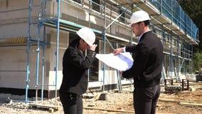 Zwei Architekten in den wei?en Sturzhelmen besprechen einen Plan an einer Baustelle stock footage