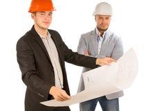 Zwei Architekten, die einen Gebäudeplan studieren Lizenzfreie Stockfotos
