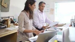 Zwei Architekten, die mit Plänen im Büro zusammenarbeiten stock video footage