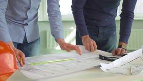 Zwei Architekten machen Kennzeichen auf den Plänen des Gebäudes stock video