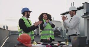 Zwei Architekten und ein afrikanisches ethnisches Ingenieurdame, den Geburtstag der Dachspitze der Baustelle feiernd sie stock footage