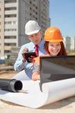 Zwei Architektenarbeiten vor Baustelle stockbilder