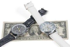 Zwei Armbanduhren auf Dollar stockbilder