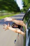Zwei Arme, die aus dem Auto heraus haften Stockfotografie