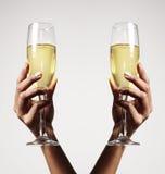 Zwei Arme mit einem Champagner im Glas Stockfotos