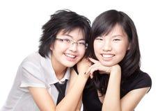 Zwei asiatische chinesische Mädchen, die einen Masseverbindermoment teilen Lizenzfreie Stockfotografie