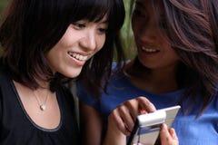 Zwei asiatische Freundinnen, die ein Mobiltelefon betrachten stockfotos