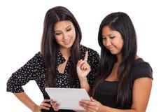 Zwei asiatische Geschäftsfrauen, die Tabletteeinheit betrachten Stockfoto