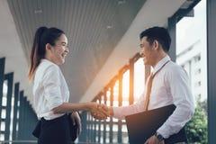 Zwei asiatische Geschäftsleute, die Hände mit zusammen stehen und rütteln stockfoto