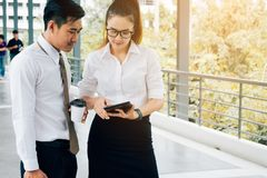 Zwei asiatische Geschäftsleute, die zusammen an digitaler Tablette an arbeiten stockfoto