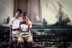 Zwei asiatische Jungen, die Schuluniformen tragen, spielen Spiel aber sie Lizenzfreie Stockbilder