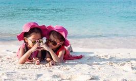 Zwei asiatische Kindermädchen, die rosa Hut und die Sonnenbrille spielt mit Sand und zusammen macht Handherzform auf dem Strand  lizenzfreie stockfotos