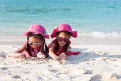 Zwei asiatische Kindermädchen, die rosa Hut und die Sonnenbrille zusammen spielt mit Sand auf dem Strand nahe dem schönen Meer  stockfotos